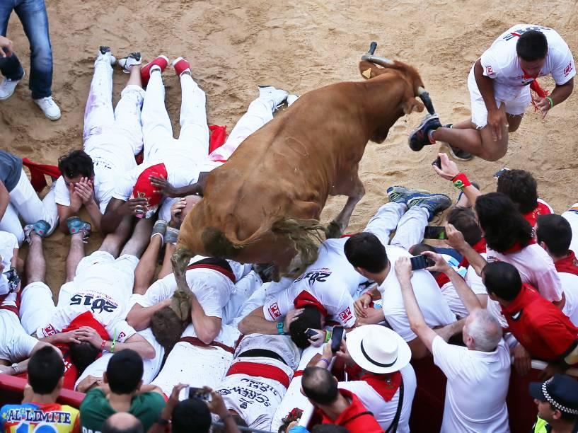"""Um touro pula por cima de participantes durante o primeiro """"encierro"""", a famosa corrida de touros do Festival de São Firmino, em Pamplona, Espanha"""