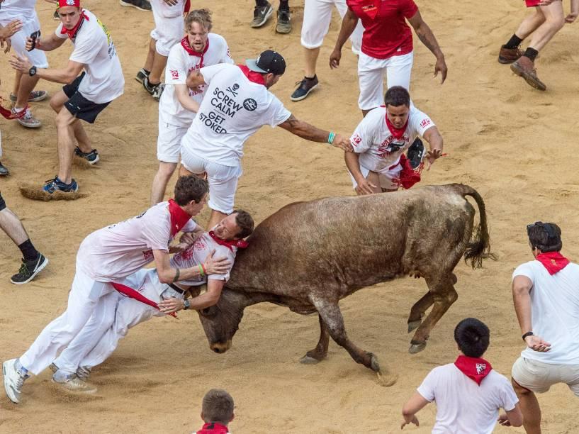 """Foliões tentam se esquivar dos touros durante o """"encierro"""", a famosa corrida de touros do Festival de São Firmino, em Pamplona, Espanha"""