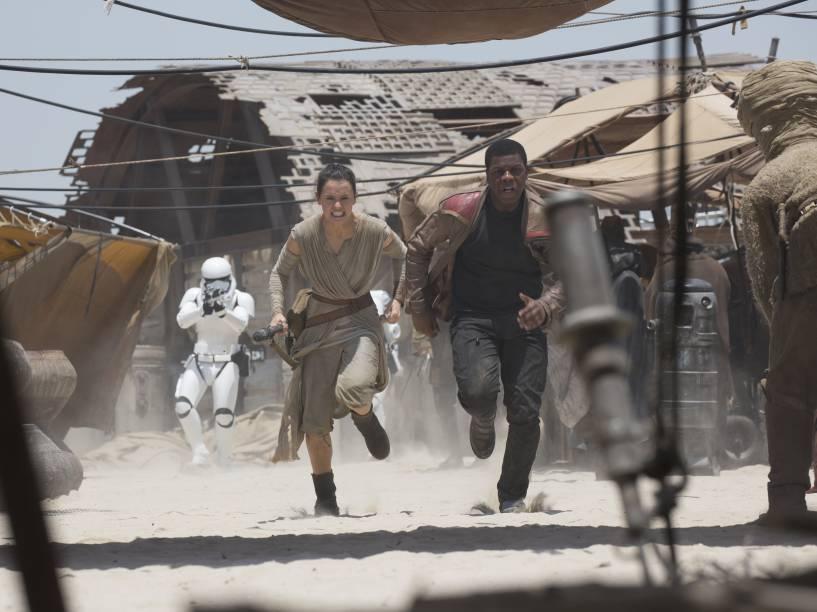Rey (Daisy Ridley) e Finn (John Boyega) fogem das tropas do Império no deserto de Jakku em cena do filme Star Wars: Episódio VII - O Despertar da Força