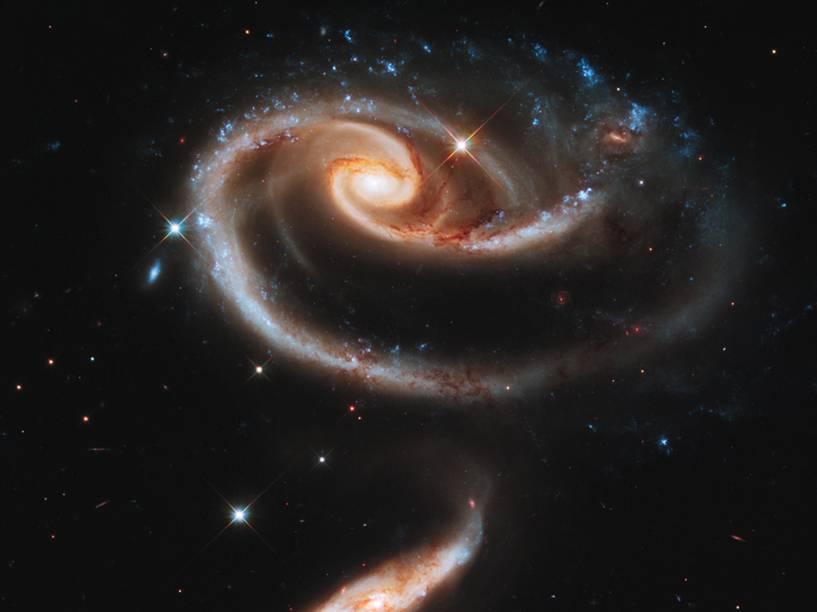 <p>Duas galáxias interagindo gravitacionalmente formando uma rosa celestial</p>