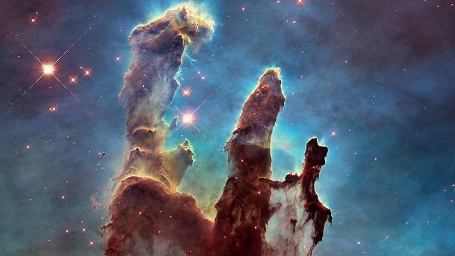 <p>As três colunas de gás se encontram na região da Nebulosa de Águia, um jovem aglomerado estelar. A foto, conhecida como Os pilares da criação, tinham uma primeira versão de 1995 e foi refeita em 2014</p>