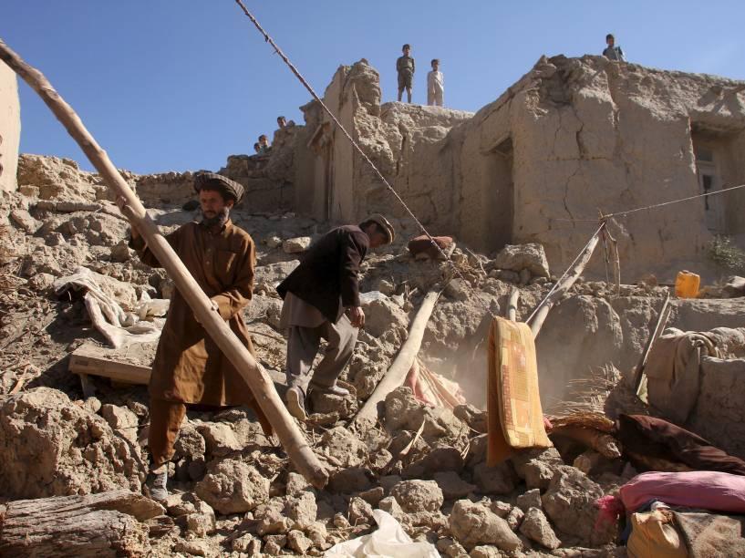 Homens recolhem seus pertences em meio aos destroços após terremoto que atingiu o norte do Afeganistão - 27/10/2015
