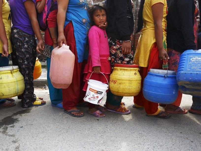 Pessoas aguardam na fila para pegar água próximo a abrigos improvisados para ajudar as vítimas do terremoto que atingiu Katmandu no sábado (25)