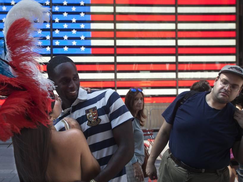 Homem olha mulher que posa com pintura corporal na Times Square. O prefeito de Nova York pensa em medidas para acabar com a atividade