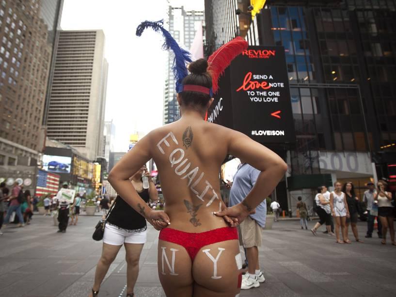 Mulheres fazendo topless posam com turistas em troca de gorjetas na Times Square, Nova York