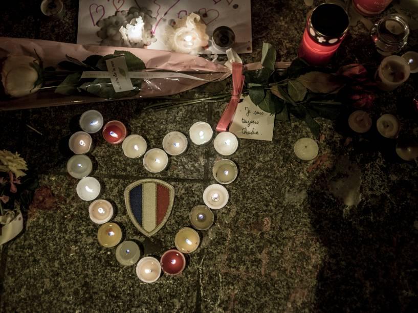 Pessoas acendem velas em homenagens às vítimas dos atentados aos restaurantes Le Petit Cambodge e o Le Carillon em Paris