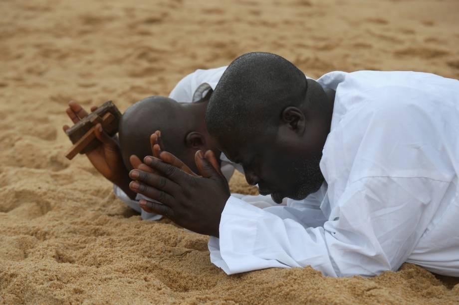 Fiéis são fotografados rezando na praiade Aladura, na província deMonróvia, na Libéria. O país passa por uma crise humanitária desde que o vírus Ebola se expalhou em todo o território nacional