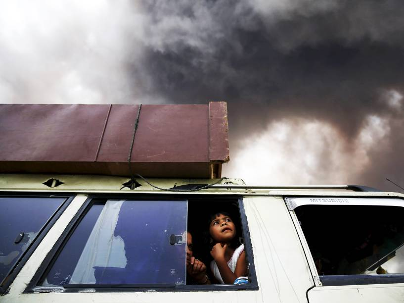 <p>Família deixa área de zona de perigo durante uma erupção do vulcão do Monte Sinabung em Karo Regency, no norte de Sumatra, na Indonésia</p>