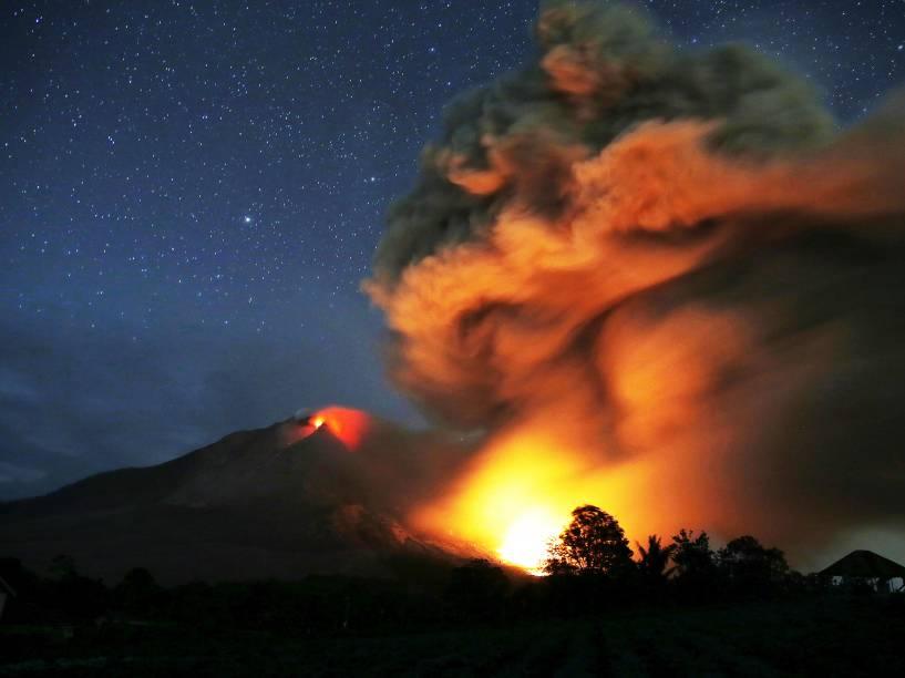 <p>Monte Sinabung expele lava em foto tirada a partir de uma aldeia vazia em Karo, província de Sumatra do Norte, na Indonésia - 25/06/2015</p>