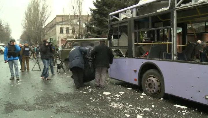 Pessoas carregam uma vítima de um projétil que atingiu um trólebus, em Donetsk