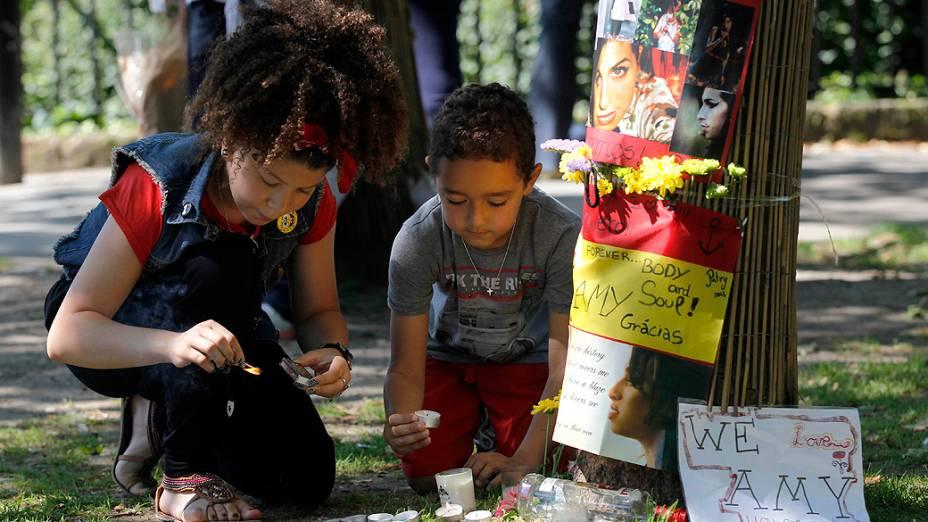 Jovens fãs da cantora Amy Winehouse acendem velas para homenagear a cantora