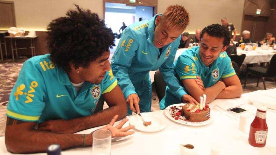 Neymar distribui fatias de seu bolo de aniversário aos colegas Dante e Fred, na concentração da seleção brasileira