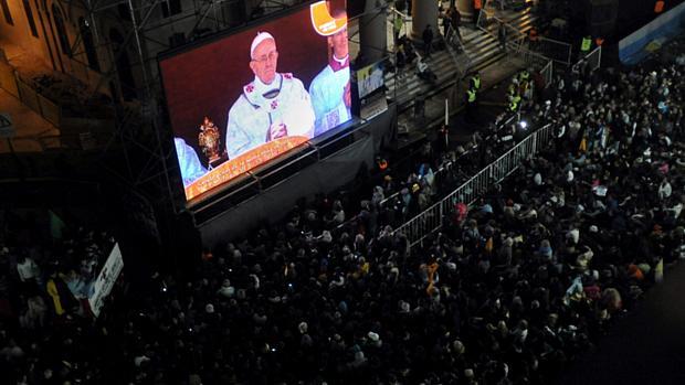 Católicos acompanham por um telão instalado em frente à catedral de Buenos Aires, Argentina, a missa de início do pontificado do papa Francisco