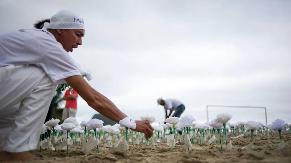 """Ativistas plantam flores na areia para comemorar os 10 anos do projeto """"Manifesto da Flores"""" (Manifesto da flor) na praia de Copacabana, Rio de Janeiro"""