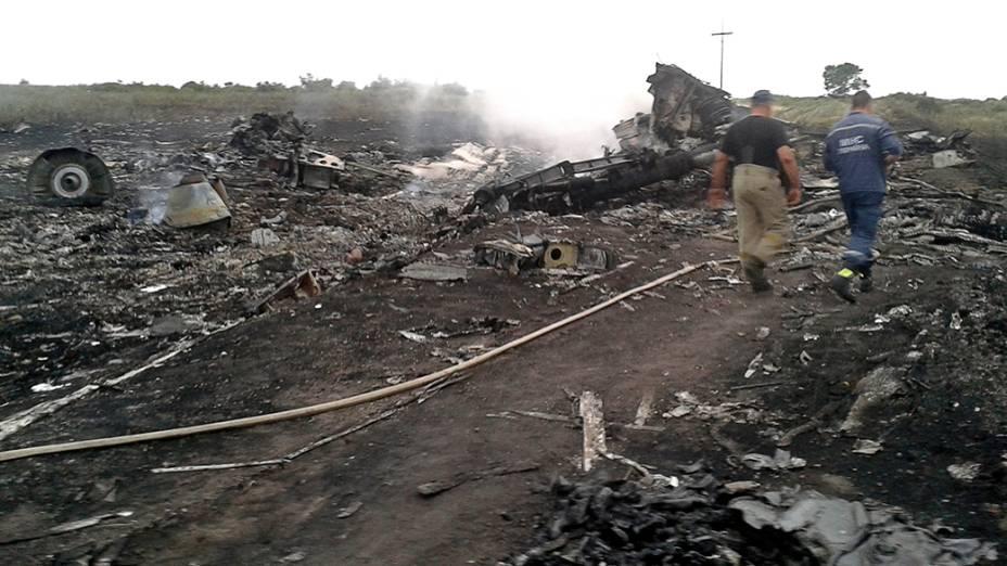 Oficiais do Ministério de Emergências trabalham no local onde o Boing 777 da Malaysia Airlines caiu na região de Donetsk, na Ucrânia oriental. Segundo as autoridades, o avião foi abatido sobre o território por militantes pró-Rússia, matando as 295 pessoas que estavam a bordo