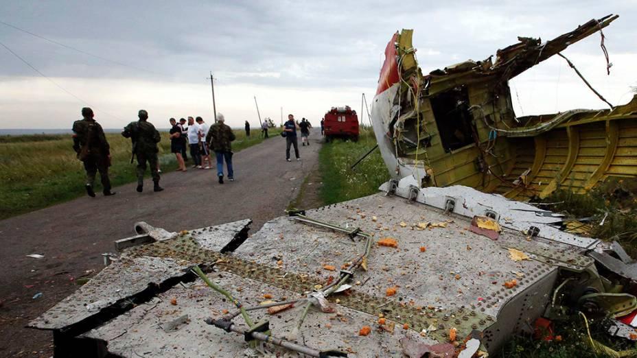 Pessoas são vistas próximo aos destroços do avião da Malaysia Airlines que caiu, em uma região controlada por rebeldes pró-Rússia no leste da Ucrânia