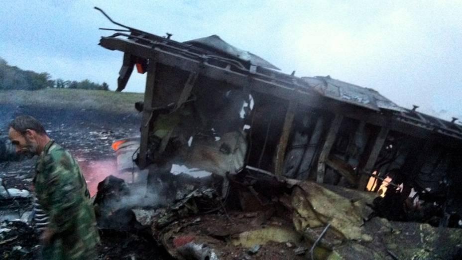 Homem é fotografado ao lado dos destroços do Boing 777 da Malasya Airlines, abatido na região de Donastek, na Ucrânia oriental. A aeronave saiu de Amsterdão rumo a Kuala Lumpur e transportava 298 passageiros