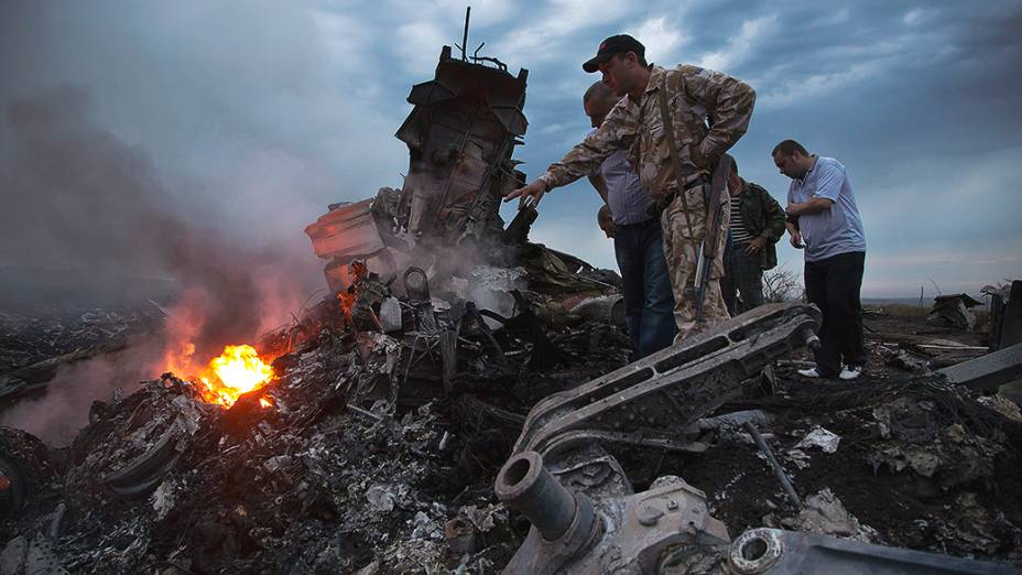 Pessoas observam o local onde o avião da Malaysia Airlines caiu na região de Donetsk, na Ucrânia oriental