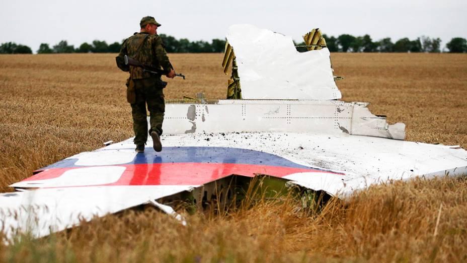 Separatista pró-Moscou anda sobre um destroço do Boeing 777 da Malaysia Airlines que caiu na região de Donetsk, na Ucrânia oriental