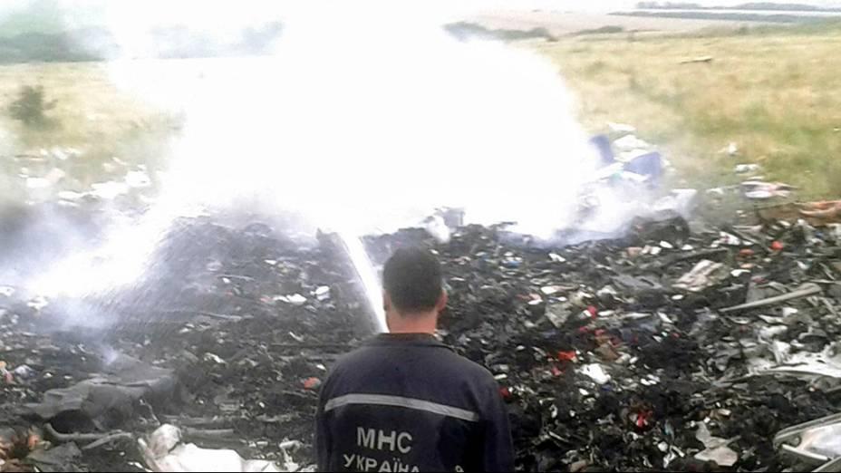 Oficiais do Ministério de Emergências trabalham no local onde o Boing 777 da Malaysia Airlines caiu na região de Donetsk, na Ucrânia oriental. Segundo as autoridades, o avião foi abatido sobre o território por militantes pró-Rússia, matando as 298 <br>pessoasque estavam a bordo