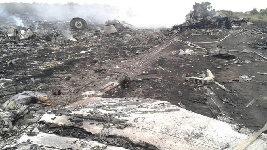 Oficiais do Ministério de Emergências trabalham no local onde o Boing 777 da Malaysia Airlines caiu na região de Donetsk, na Ucrânia oriental. Segundo as autoridades, o avião foi abatido sobre o território por militantes pró-Rússia, matando as 298<br> pessoas que estavam a bordo