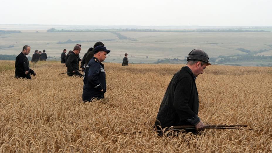 Um grupo de mineiros ucranianos ajuda equipes de resgate na busca dos corpos das vítimas em um campo de trigo no local da queda de um avião transportando 298 pessoas que seguia de Amsterdã para Kuala Lumpur, em Grabovka, na Ucrânia