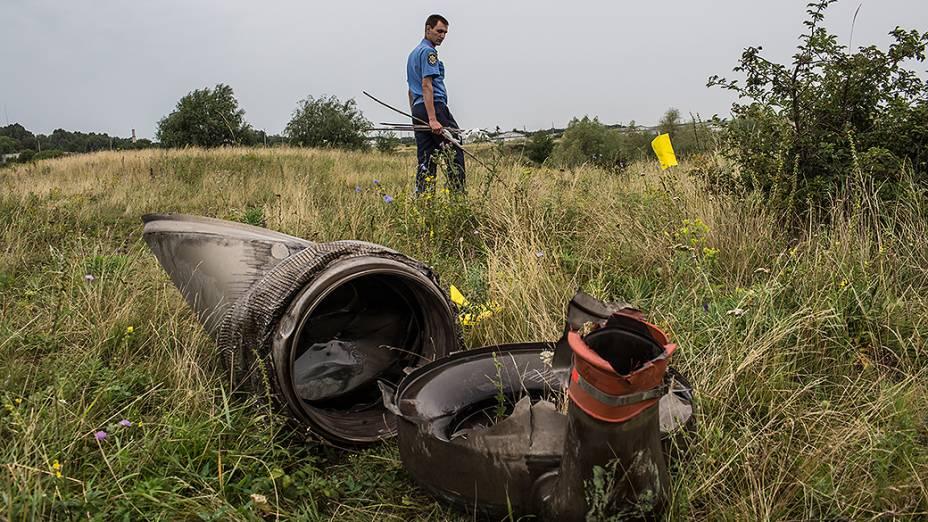 Policial trabalha na busca por corpos no local onde o avião da Malaysia Airlines foi abatido, em Grabovka, Ucrânia