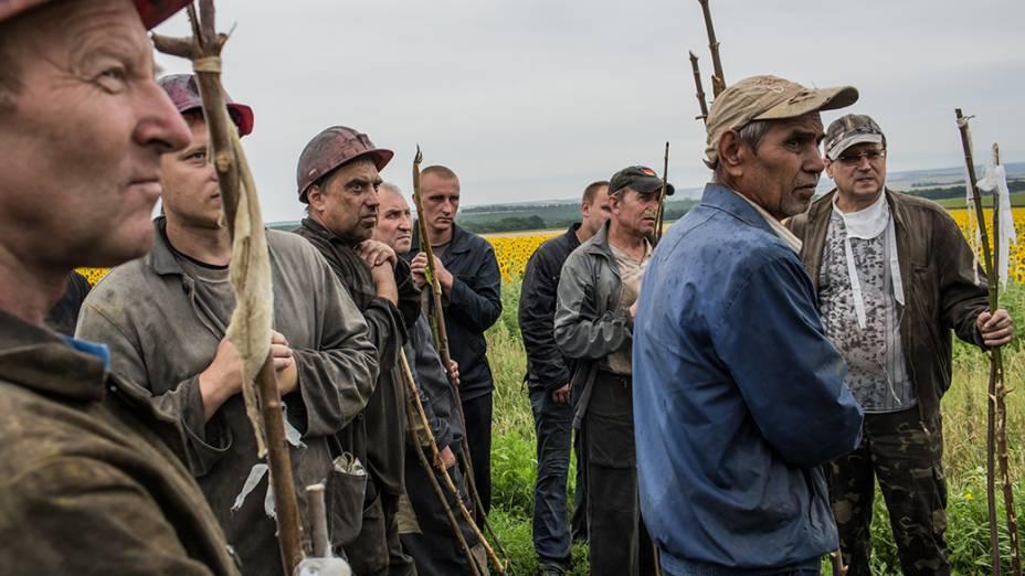 Um grupo de mineiros ucranianos ajuda equipes de resgate na busca dos corpos das vítimas no local da queda de um avião transportando 298 pessoas que seguia de Amsterdã para Kuala Lumpur, em Grabovka, na Ucrânia