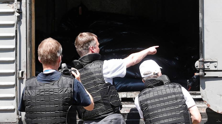 Agentes da Organização para a Segurança e Cooperação na Europa inspecionamum vagão frigorífico, que de acordo com funcionários e moradores locais,contém corpos de passageiros do acidentado Boing 777 da Malaysia Airlines, em uma estação de trem na cidade de Torez, região de Donetsk, ao leste da Ucrânia. A operação de retirada dos corpos das vítimas começou ontem (19)e deve seguir nos próximos dias