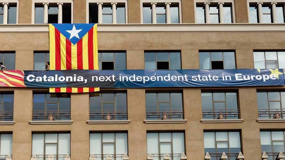 Membros da plataforma pró-independência catalã penduram bandeira gigante na Plaza de Catalunya em Barcelona