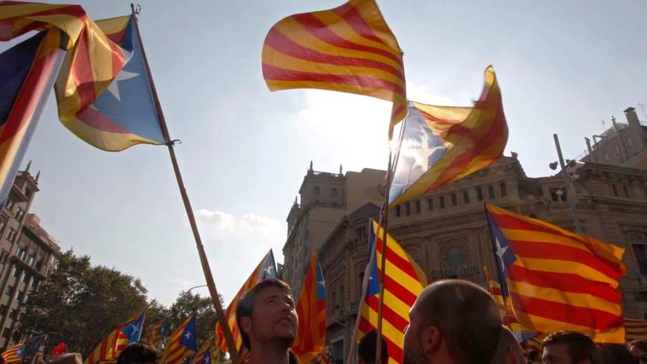 Os manifestantes nacionalistas catalães com bandeiras durante Dia Nacional da Catalunha em Barcelona