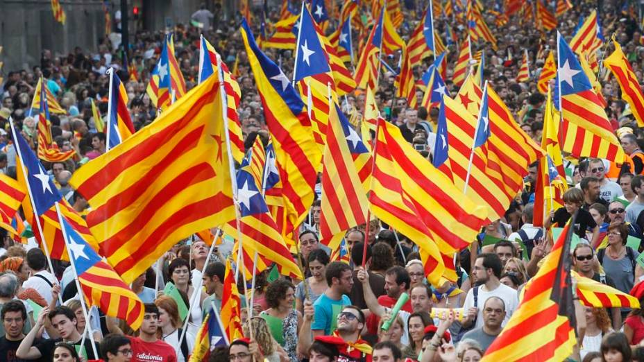 Manifestantes com bandeiras catalãs, durante o Dia Nacional da Catalunha