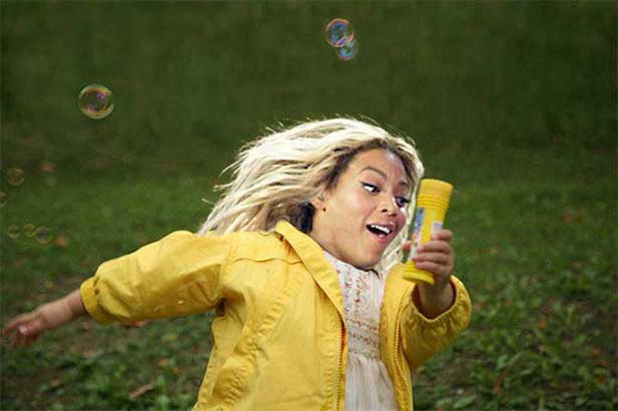 A pequena Beyoncé saltita feliz entre bolhas de sabão