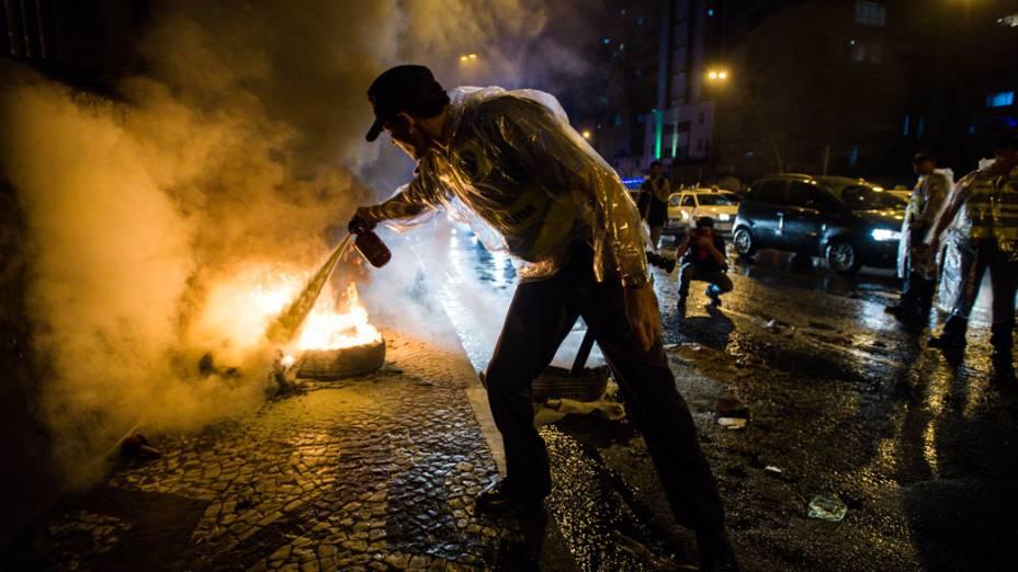 Policiais combatendo fogo deixado por manifestantes, durante ato contra o aumento da passagem