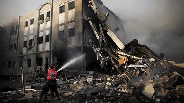Bombeiros tentam extinguir fogo no prédio do Ministério do Interior palestino em Gaza, atingido por foguetes israelenses
