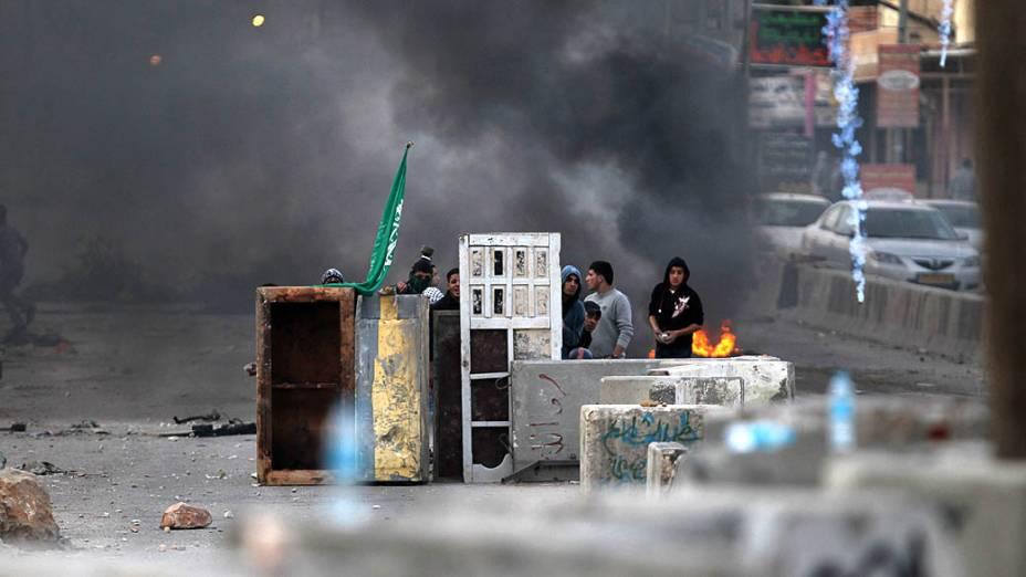 Jovens palestinos se escondem após confronto com soldados israelenses, na Cisjordânia