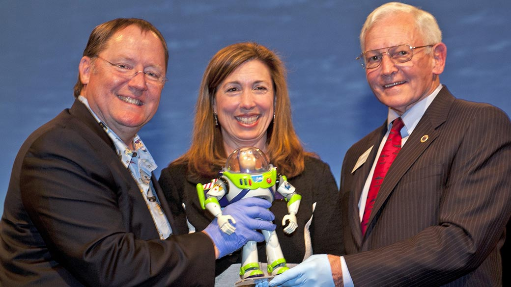 "Boneco ""Buzz Lightyear"" do filme ""Toy Story"" doado à NASA, entre John Lasseter, da Pixar; a vice-diretora da Nasa, Lori Garver; e o diretor do Museu do Ar e do Espaço do Instituto Smithsonian, Jack Dailey"