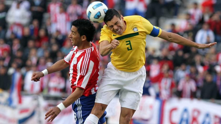 Marcelo Estigarribia, do Paraguai, e Lúcio disputam bola durante jogo das quartas de final da Copa América