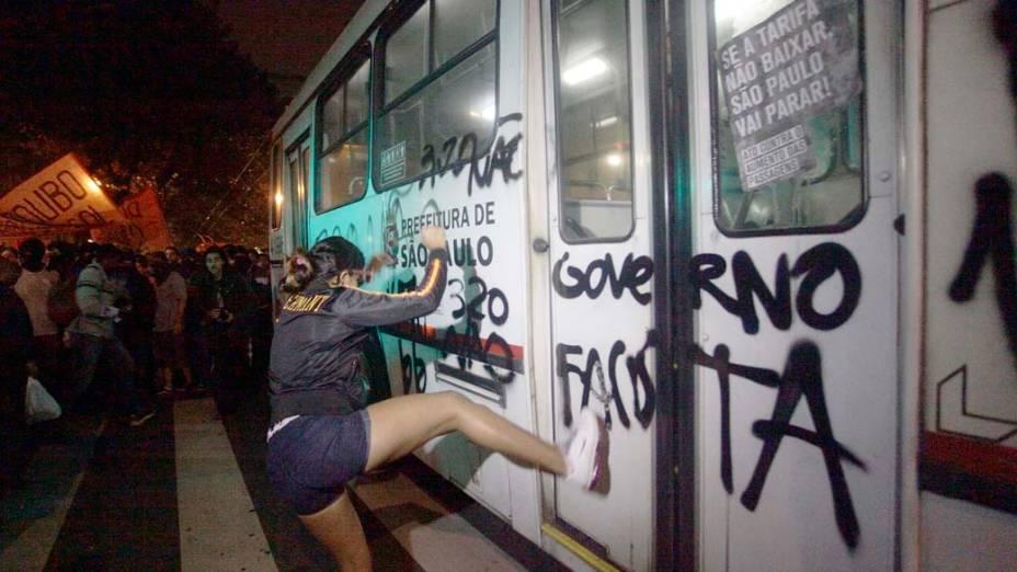 Manifestante chuta um ônibus no protesto contra o aumento da passagem de ônibus