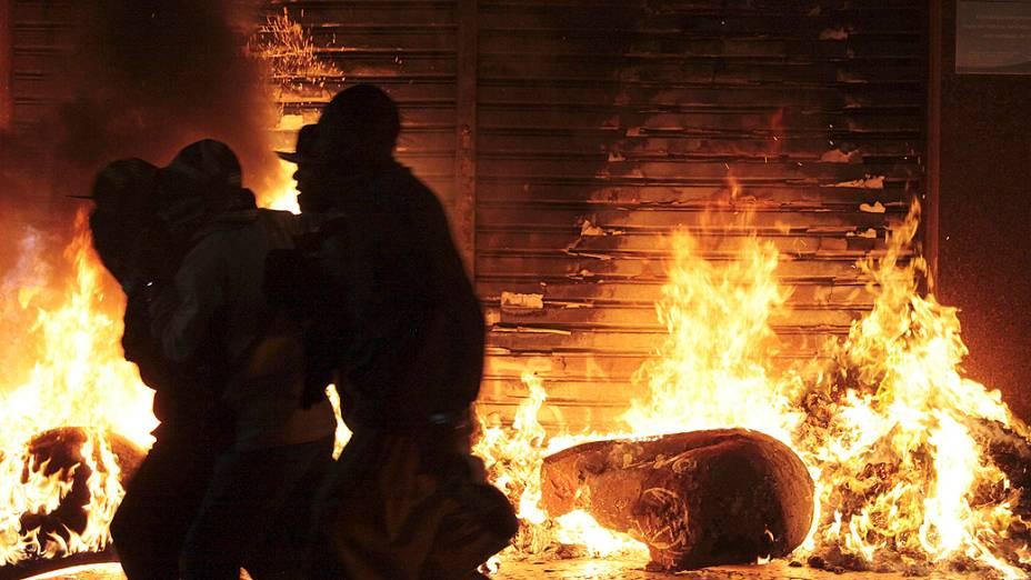 São Paulo - Vândalos se aproveitam da movimentação durante protestos contra o aumento das tarifas do transporte público, para saquear e atear fogo na porta de uma loja no centro de São Paulo