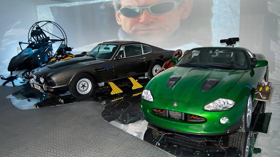 """Aston Martin V8 Volante – Em sua primeira aparição como James Bond, em """"007 – Marcado para a Morte"""", de 1987, Timothy Dalton abusa dos brinquedinhos instalados em um V8 Volante (à esquerda). Cubo de roda que dispara raios laser, mísseis escondidos no para-choque, motor a jato para dar aquela forcinha nas aceleradas e, por fim, pares de esquis para andar no gelo são alguns deles. Durante as filmagens da perseguição sobre a neve, em Weissensee, na Áustria, um dos carros quase acabou no fundo de um lago congelado, após a camada endurecida começar a rachar"""