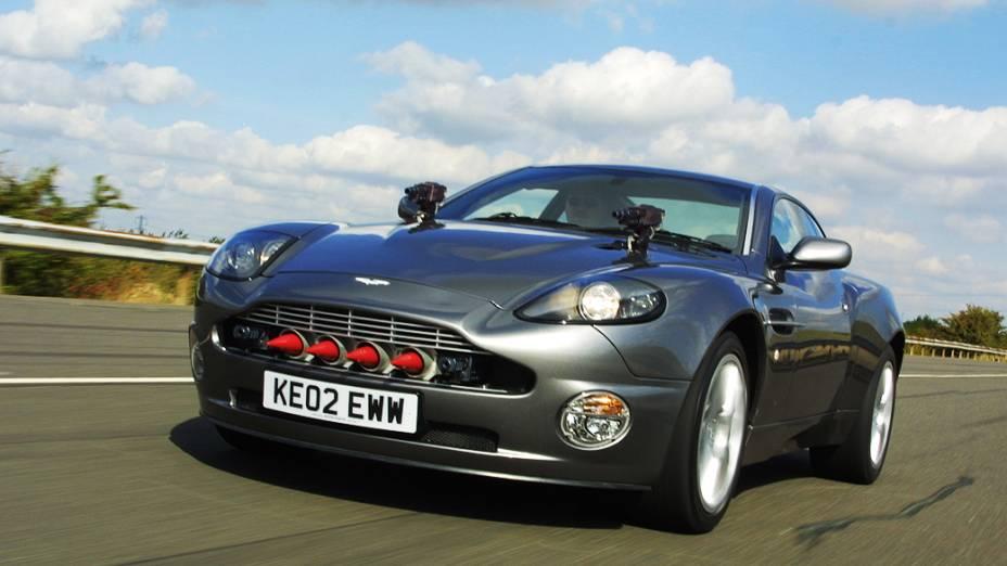 """Aston Martin V12 Vanquish – Para """"007 – Um Novo Dia para Morrer"""", o 20º filme da série, de 2002, o Aston Martin de James Bond teria de ser especial. E era. O V12 Vanquish, modelo topo de linha da época, ficava invisível ao simples toque de um botão. Também tinha metralhadoras teleguiadas escondidas sob o capô, mísseis com sensores de calor, assento ejetável, além de pneus que autoinfláveis"""