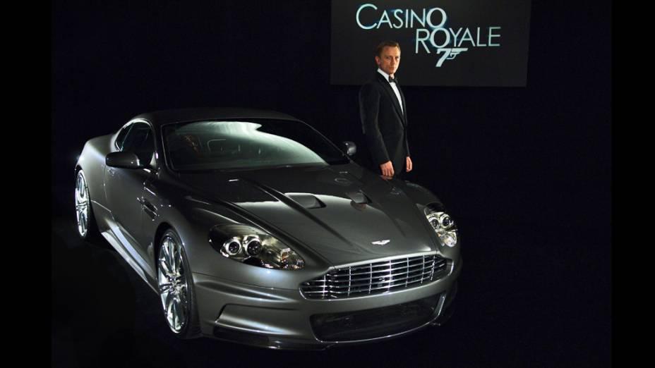 """Aston Martin DBS – O novo modelo top de linha da Aston Martin fez sua estreia na série 007 juntamente com Daniel Craig na pele do agente secreto, em """"Casino Royale"""", de 2006. Apesar do belo visual, o DBS não trazia nenhum aparato tecnológico ou armamento pesado escondido – com exceção de um computador portátil, um aparelho desfibrilador e um estojo com medicamentos. Seu design arrojado já o creditava como um legítimo Bond-car. Na cena em que o DBS capota várias vezes, a equipe de efeitos especiais teve de virar o carro na marra usando um canhão de ar comprimido instalado atrás do banco do motorista. Em """"Quantum of Solace"""", de 2008, o DBS retorna para estrelar uma perseguição de tirar o fôlego, logo no início do filme. Ao todo, sete DBS foram usados nas filmagens, realizadas nos arredores do Lago Garda e em Carrara, no norte da Itália"""