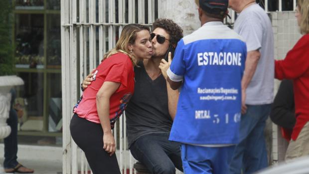 Cauã Reymond beija fã enquanto fala ao celular