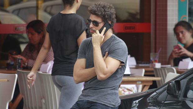 Cauã Reymond fala ao celular na Barra da Tijuca