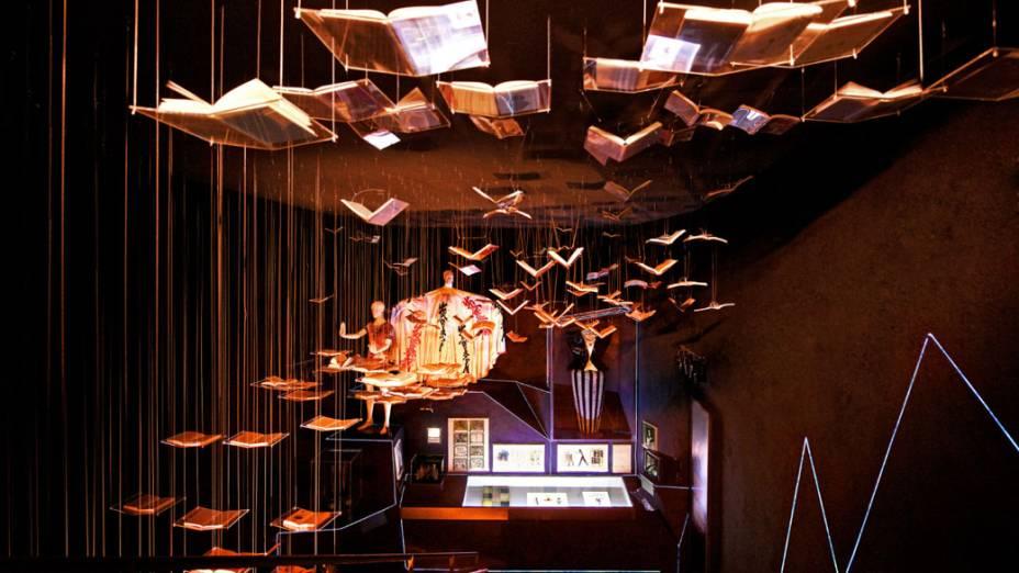 """Sala com """"livros voadores"""" destaca algumas influências de David Bowie na literatura e na moda. Ao fundo, figurinos usados na década de 1970"""
