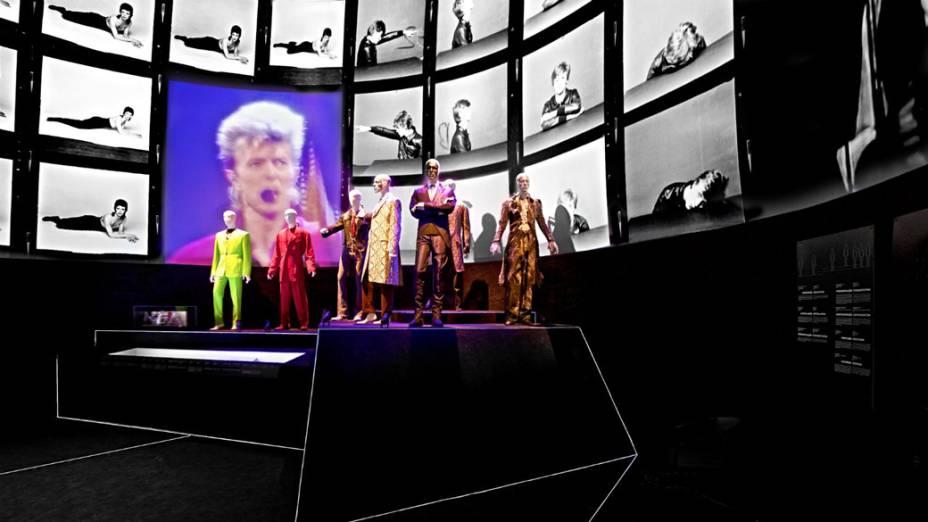 Grande sala da exposição no MIS reúne figurinos de diversas fases da carreira de David Bowie enquanto clipes passam ao fundo