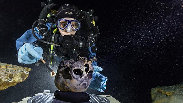 """<p>Um esqueleto encontrado em uma caverna submersa no México deu pistas sobre a ligação entre os primeiros habitantes da América e os povos indígenas que se desenvolveram no continente. O esqueleto pertence a uma menina que tinha entre 15 e 16 anos, e recebeu o apelido de Naia, que significa """"ninfa das águas"""". Na foto, a pesquisadora Susan Bird limpa o crânio, ainda no fundo da caverna onde ele foi encontrado, para que fotografias detalhadas fossem feitas</p>"""