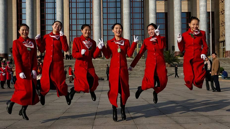 Recepcionistas do Congresso Nacional do Partido Comunista Chinês tiram foto em frente ao edifício que recebe o evento