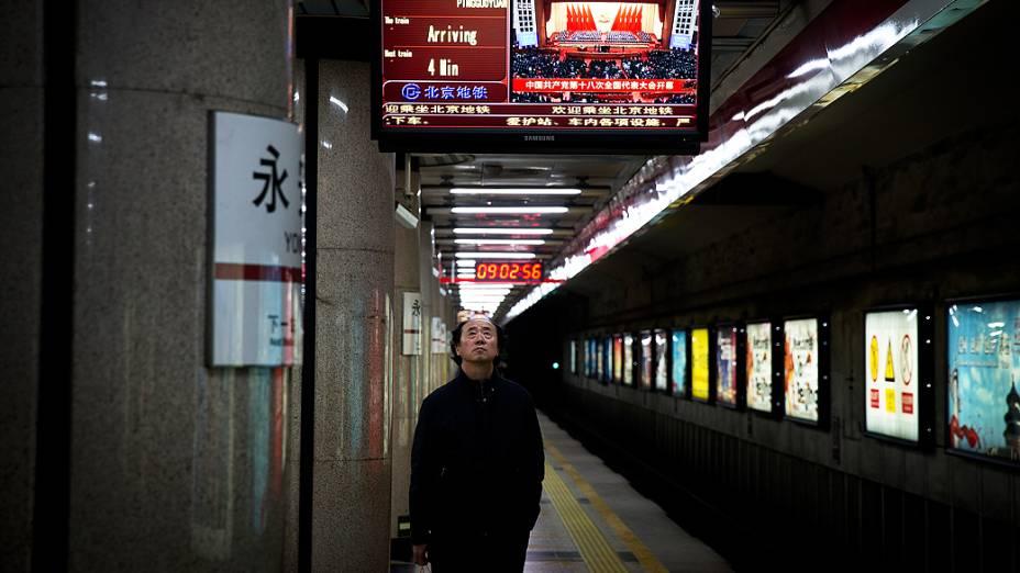Em uma estação de metrô em Pequim, homem assiste à transmissão da cerimônia de abertura do 18º Congresso do Partido Comunista